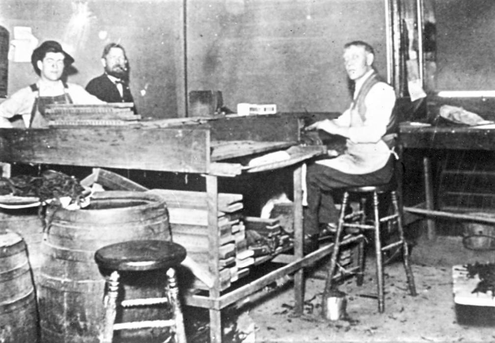 Three men sit at a table working on cigars.
