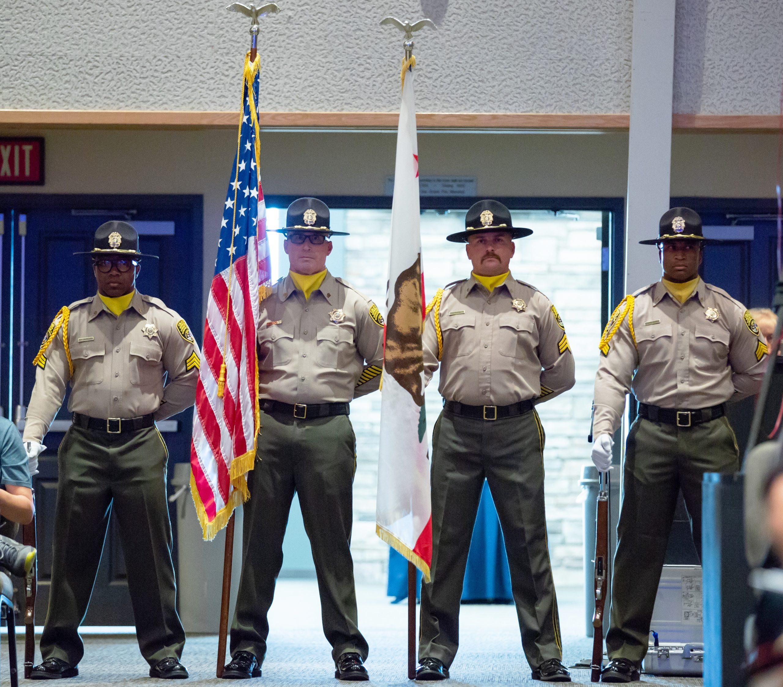 Four uniformed officers facing camera with one holding U.S. flag and another holding California flag.
