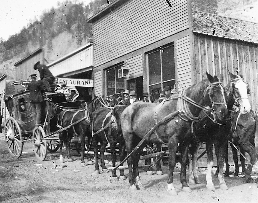Men work to ready a stagecoach being pulled by six horses.