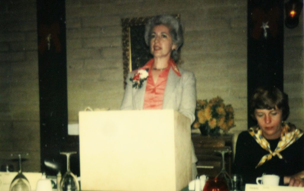 Women stands at lectern and speaks to a gathering.