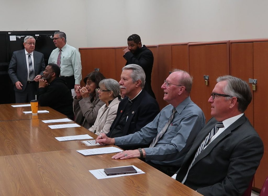 Chaplains sit at a table in a CDCR prison.
