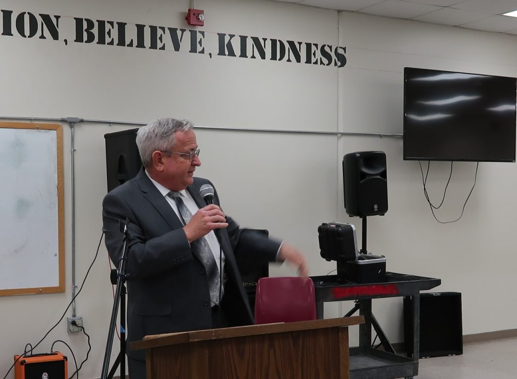 """A chaplain speaks. Behind him are painted the words """"Believe"""" and """"Kindness."""""""