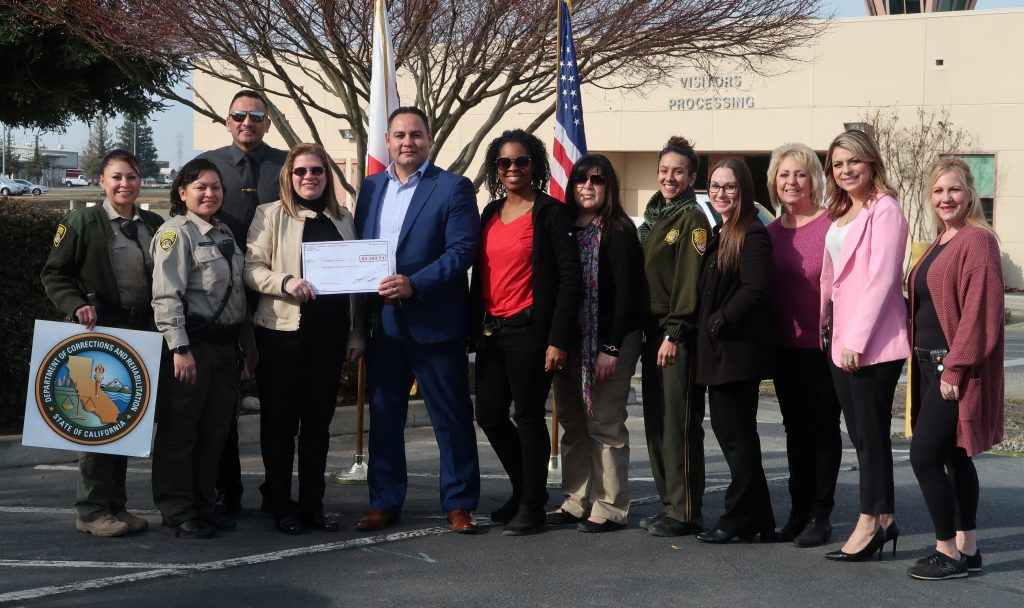CDCR employees present a check to breast cancer awareness organization. The visitor processing area can be seen behind them.