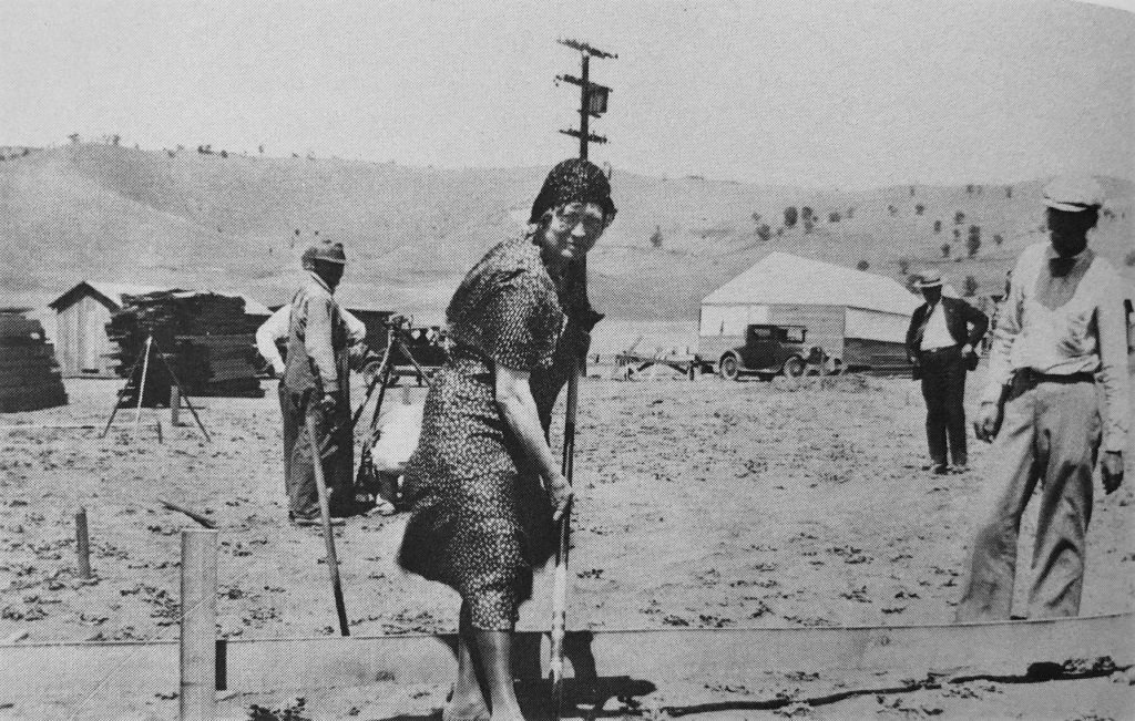 Woman in flowery dress digs some dirt at future site of women's prison.