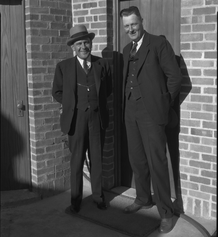 Two men stand near brick wall and doors.