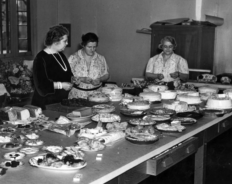 Three women stand around a table full of baked goods such as pies and cakes.