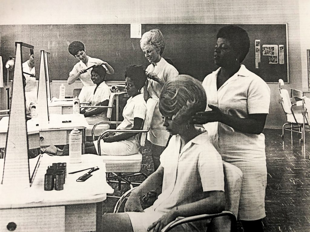 Three women practice hair styling skills on three other women at California Institution for Women.