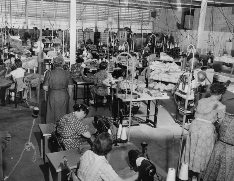 Women work in a warehouse full of sewing machines.