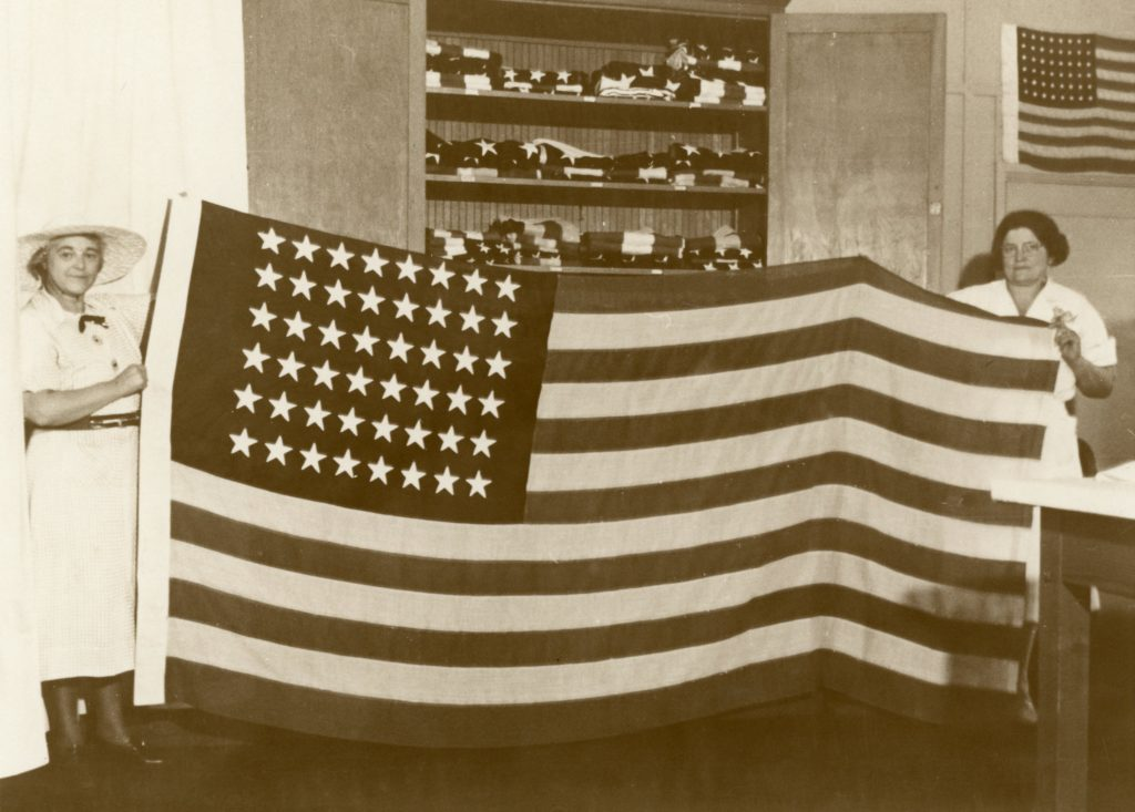 Two female inmates hold a large U.S. flag.