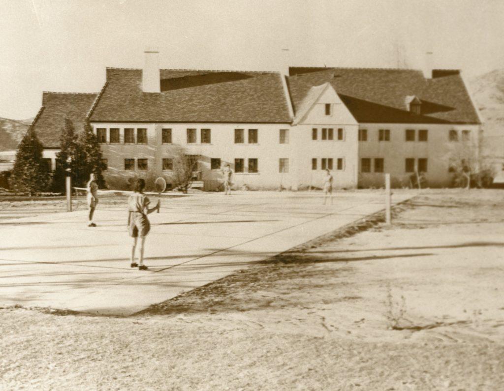 Women play tennis at women's prison.