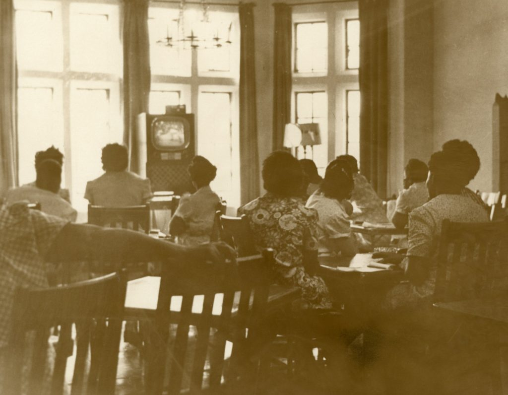 Female prison inmates watch a small television.