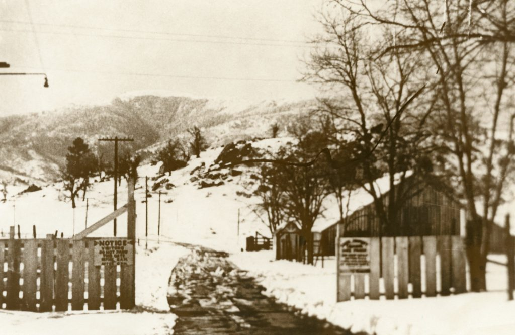 Fence and snowy hills surround prison entrance at Tehachapi.