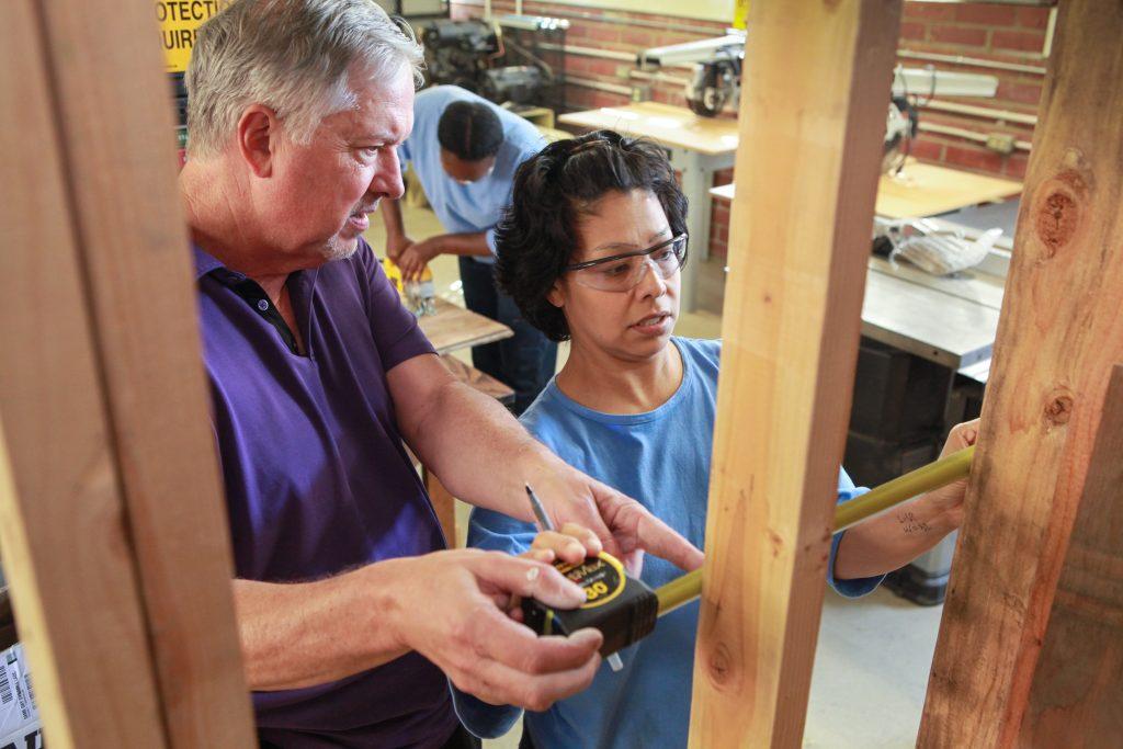 A man teaches a female inmate building maintenance skills.