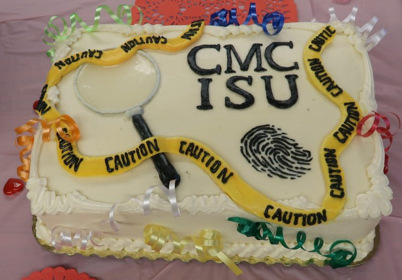 Fingerprint, caution tape and magnifying glass highlight a cake with the letters CMC ISU on it.