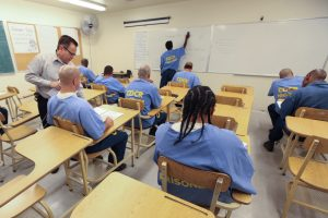 Classroom with prison inmates sitting in desks and teacher helping them.