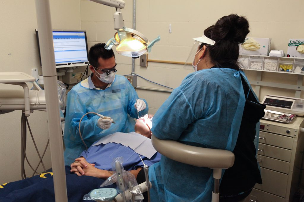 Dentist works on an inmate while dental assistant helps.