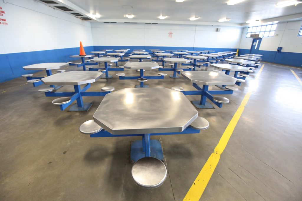 Tables with seats attached fill a room in a prison.