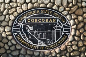 A sign for Corcoran Prison features drawings of a prison tower and buildings.