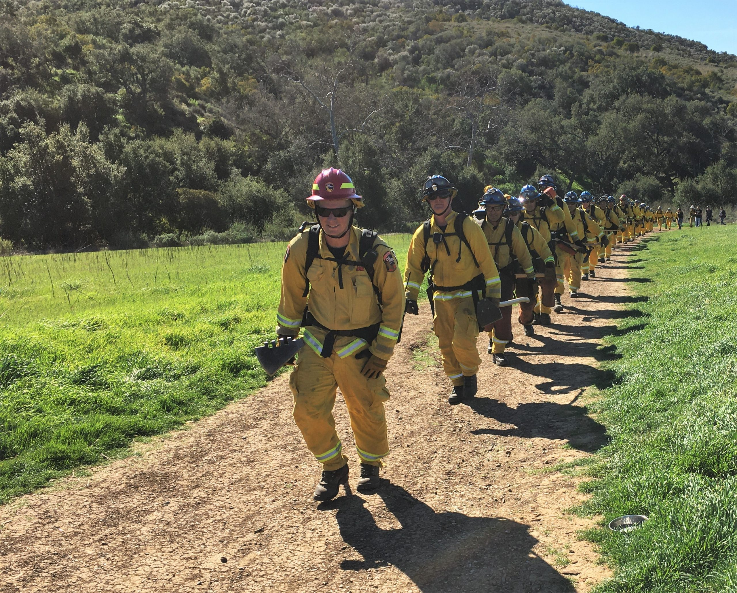 Firefighters hike on a trail in Ventura County.