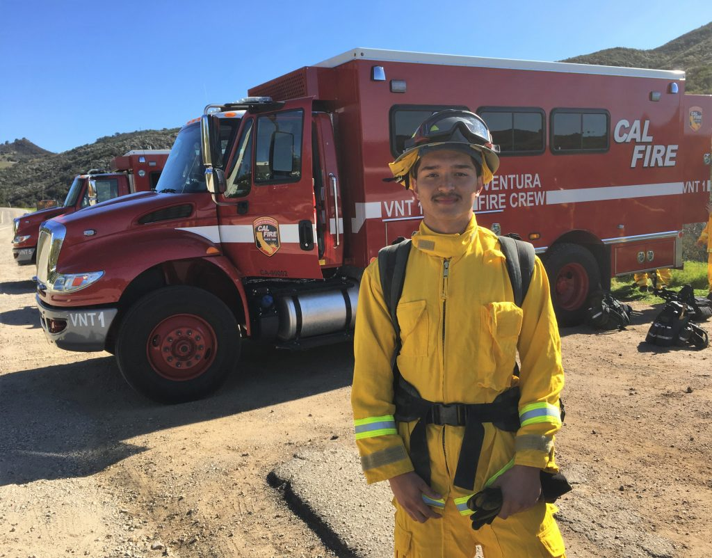 Youth firefighter poses in front of Ventura Training Center fire truck.