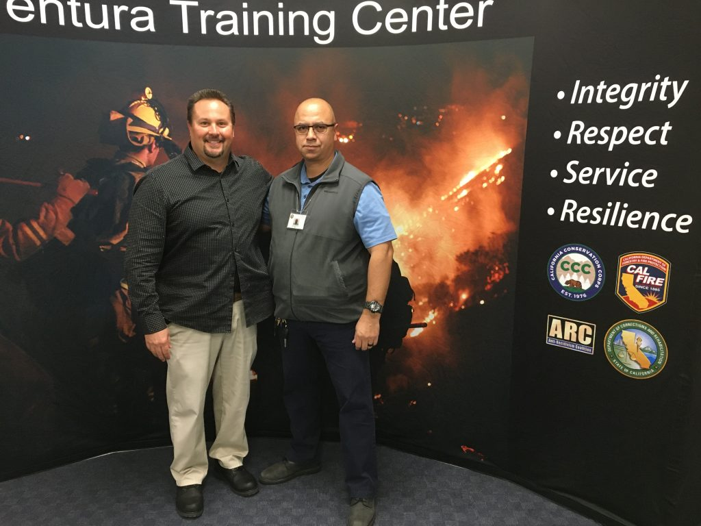 Two men stand in front of a board promoting the Ventura Training Center.