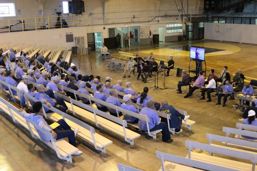 Large room in a California prison with inmates and guests.