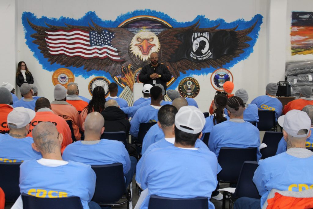 High Desert State Prison Nate Williams speaks to inmates. Behind him is a mural showing a bald eagle, the U.S. flag and a POW-MIA flag.