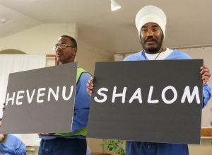 """Inmates hold signs with """"hevenu"""" and """"shalom,"""" meaning """"we brought peace."""""""