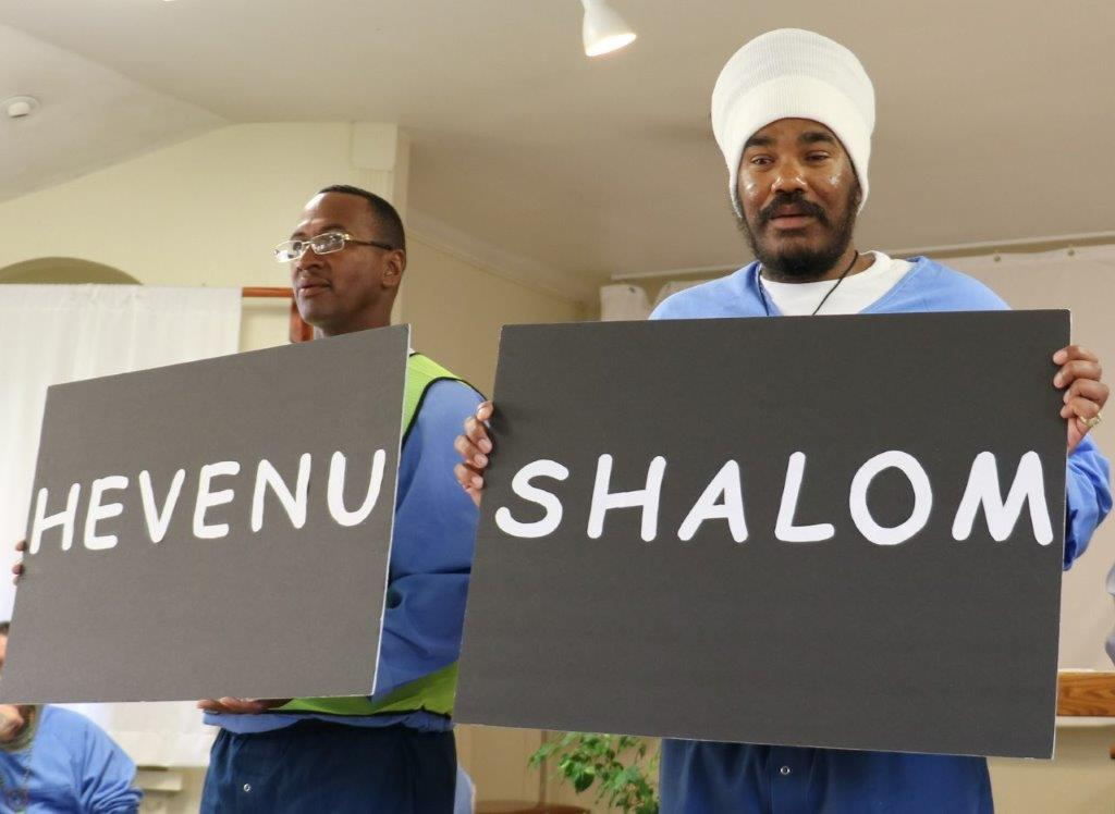 "Inmates hold signs with ""hevenu"" and ""shalom,"" meaning ""we brought peace."""