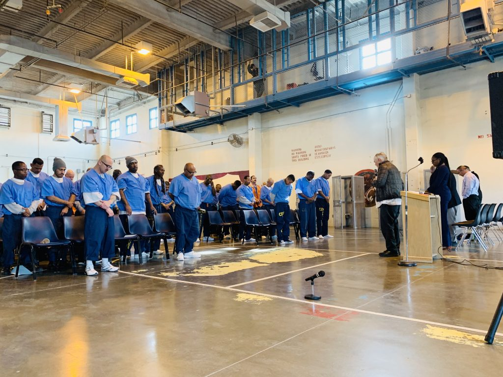 Inmates bow their heads in prayer at California State Prison, Los Angeles County