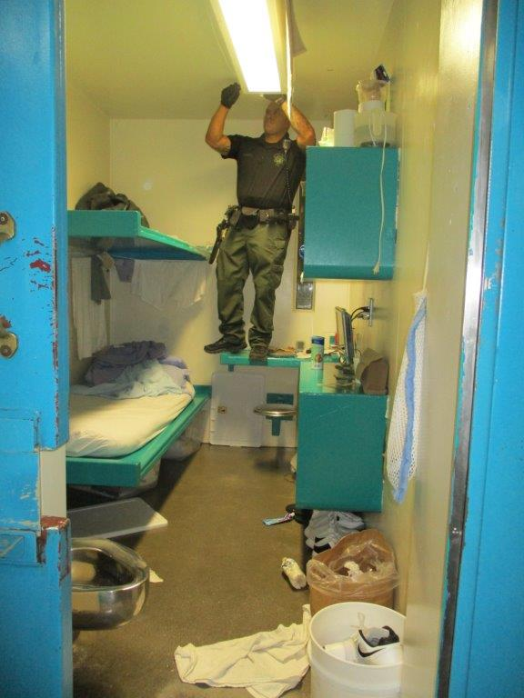 CDCR correctional officer searches a light fixture in a prison cell.