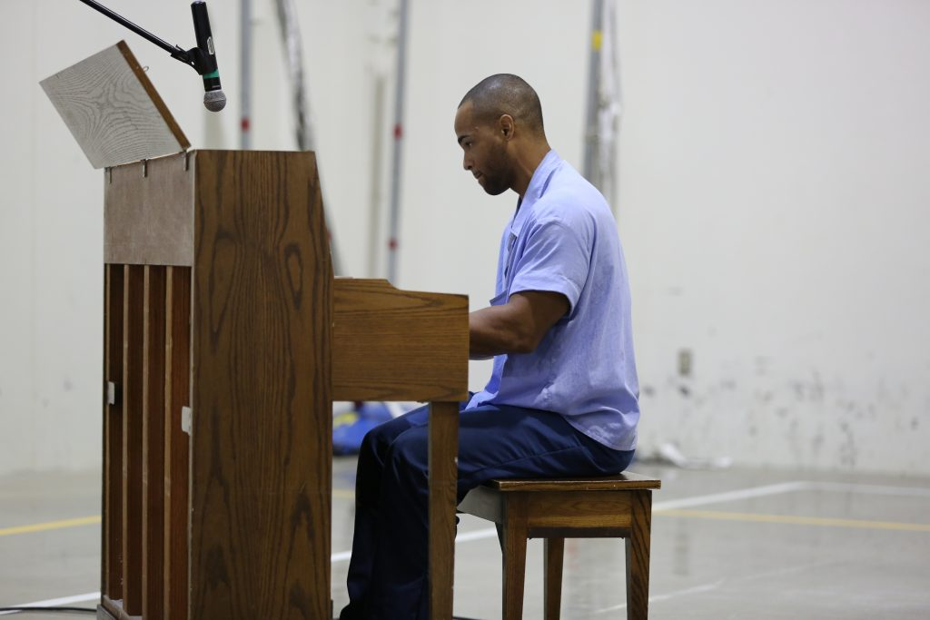 California prison inmate plays an upright piano.