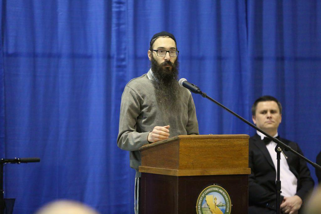 Man at lectern speaks at Mule Creek State Prison.