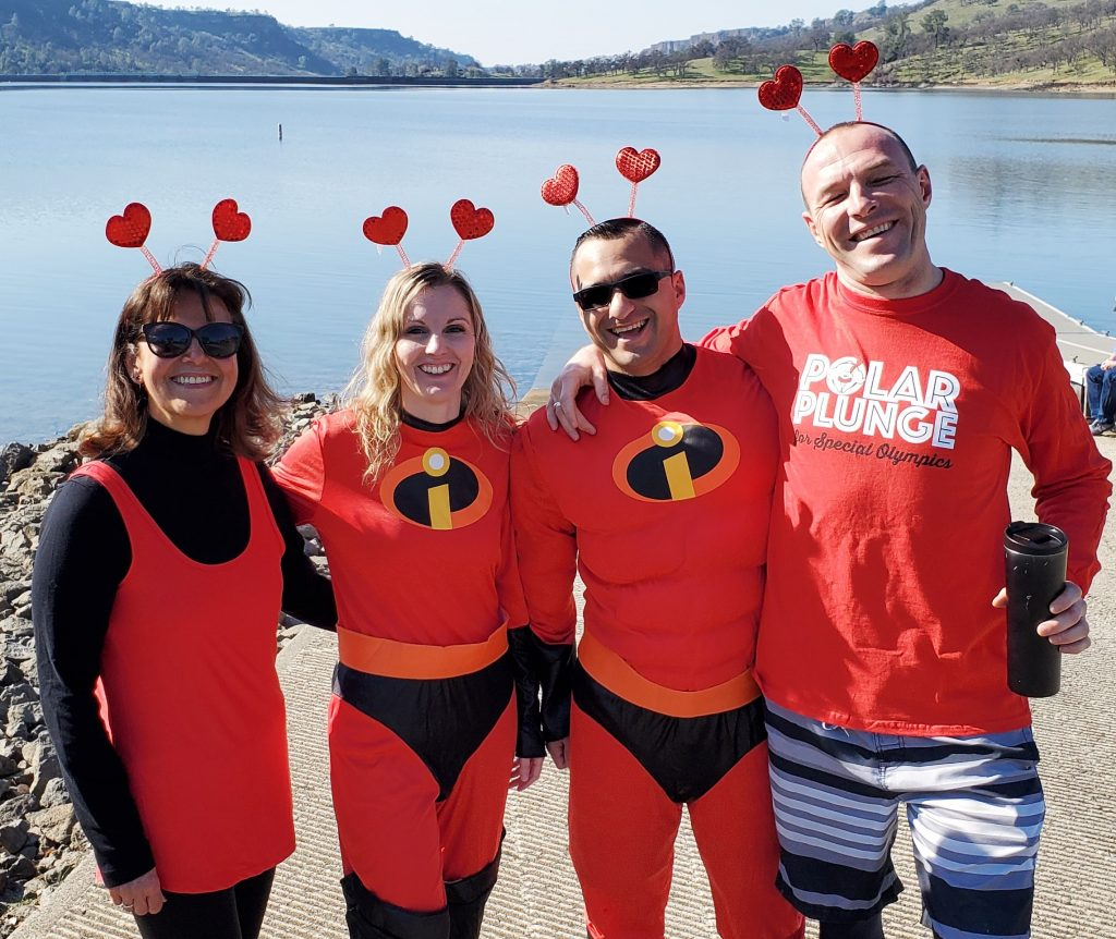Two people wear superhero costumes while to others wear similar colored clothing. Behind them is a lake.