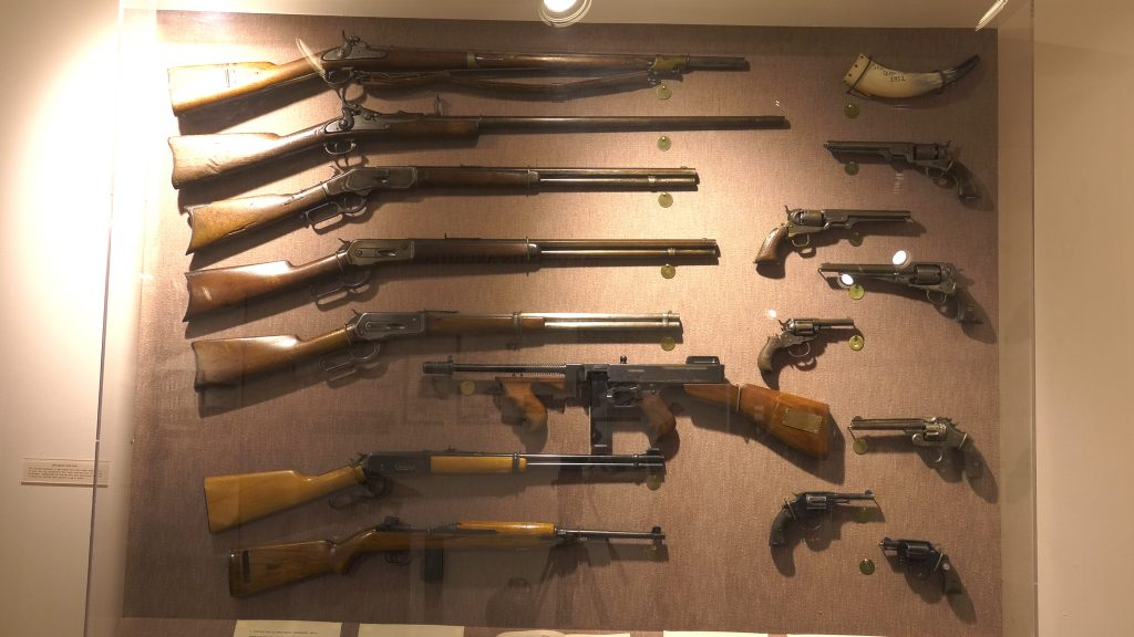 Weapons shown in a case range from pistols and powder horns to rifles and a machine gun.