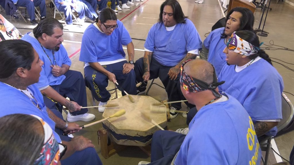 Native American inmates drum in a circle at Valley State Prison.