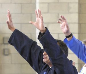 Valley State Prison inmates, staff and volunteers raise their arms during the Day of Peace and Reconciliation.