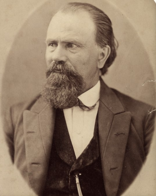 Man with beard in late 1800s period clothing.