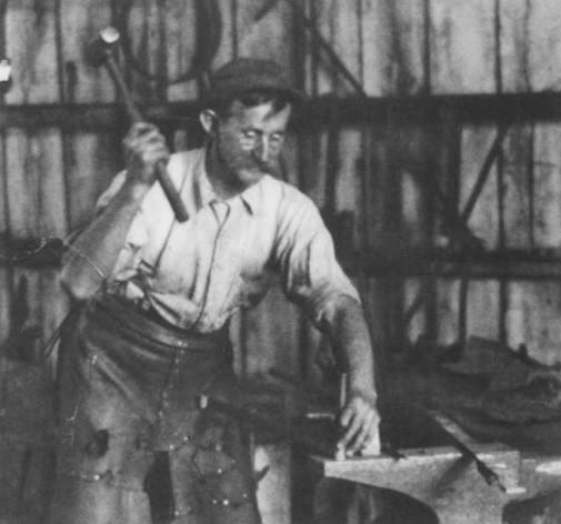 Blacksmith holds big hammer to pound something on an anvil.