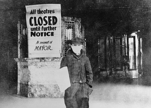 """Boy holds sign that says """"All theaters closed until further notice at request of mayor."""""""