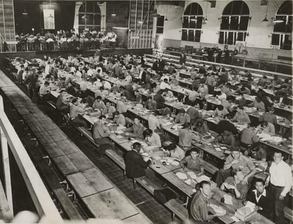 Inmates sit in the miss hall sorting World War II ration books.