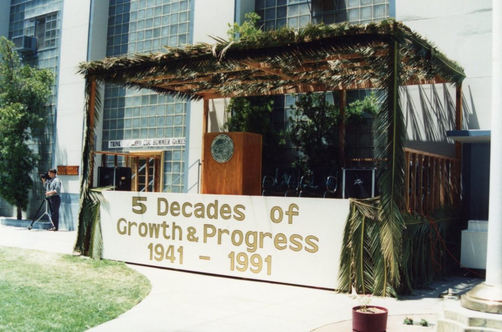 A stage with palm fronds and a sign reading 5 decades of growth and progress 1941-1991.