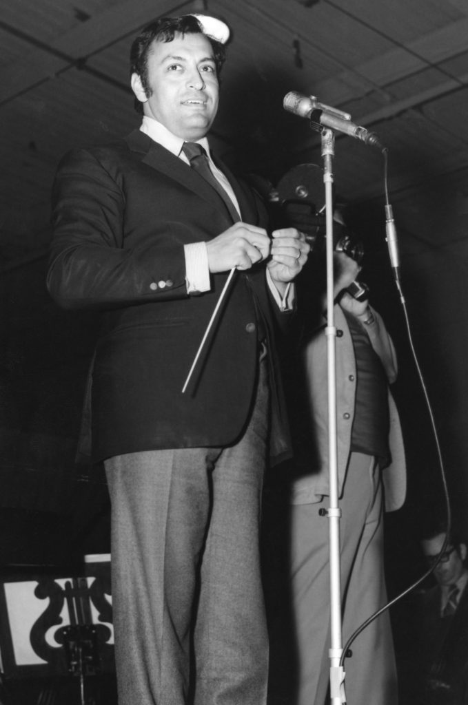Orchestra conductor Zubin Mehta stands on a stage at California Institution for Men in the 1970s.