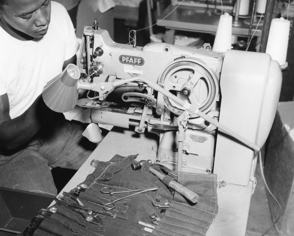 A man works on a sewing machine while tools are laid out next to him.