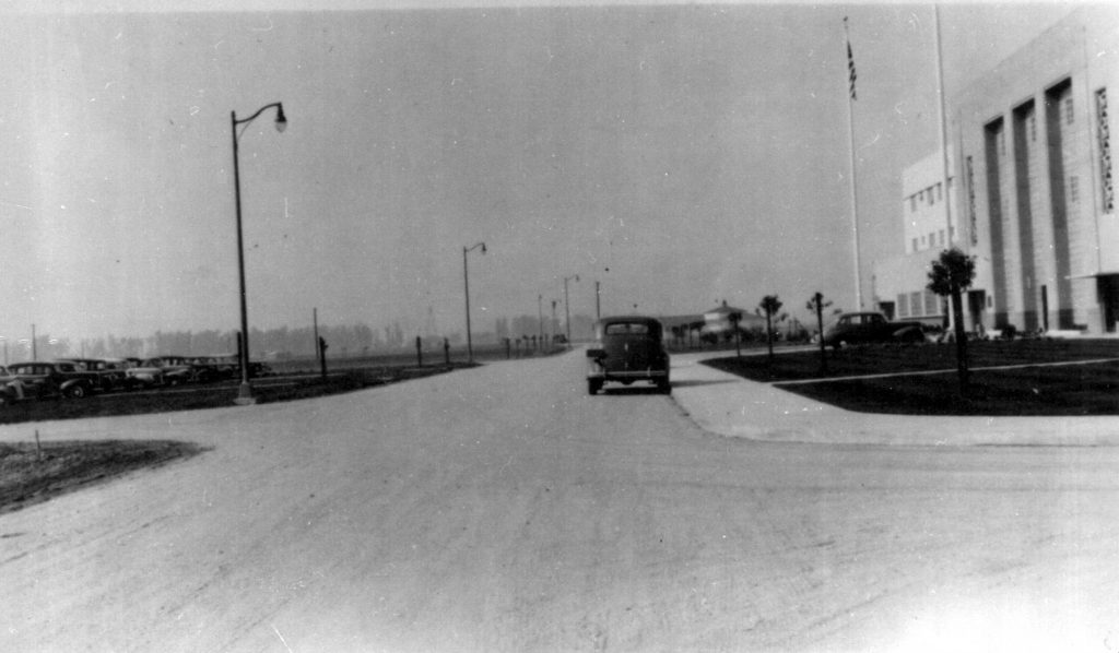 80 years ago, a 1940s style car is parked on a road in front of the prison administration building.