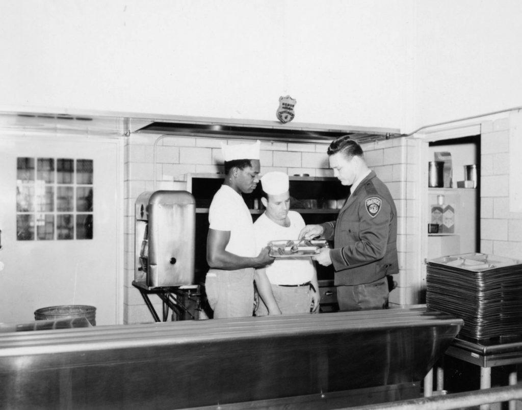 Officer checks a tray of food at CIM.