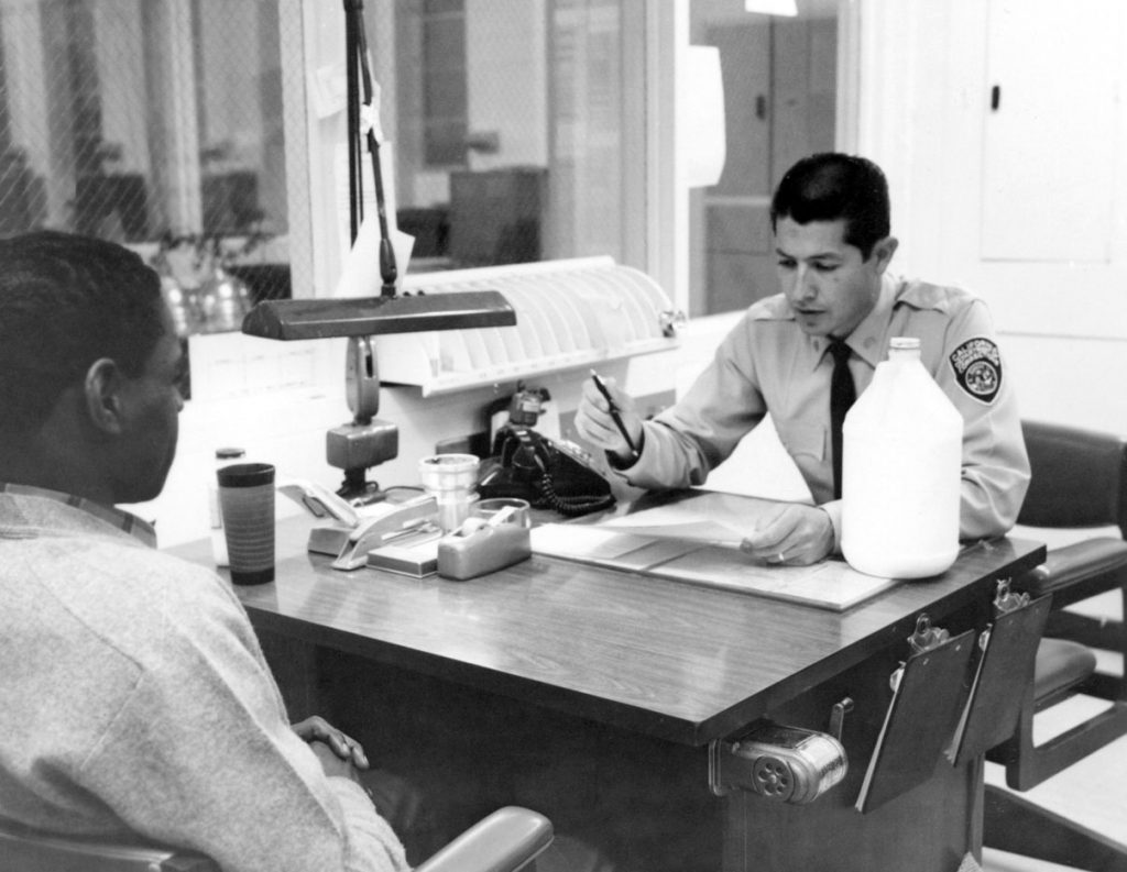An officer speaks to another man in an office at California Institution for Men.