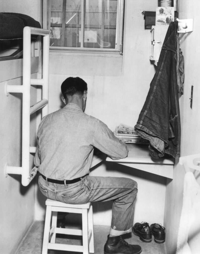 A prison inmate sits in a cell at CIM, which opened 80 years ago.