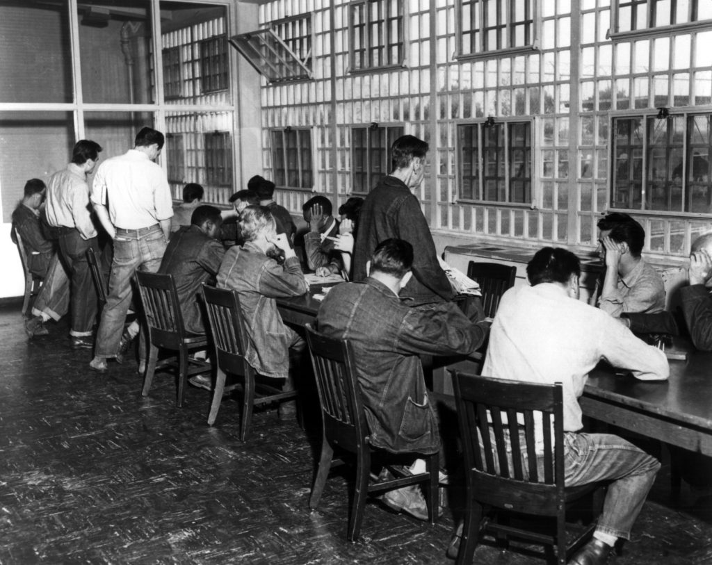 Men sit around a long table, reading and studying.