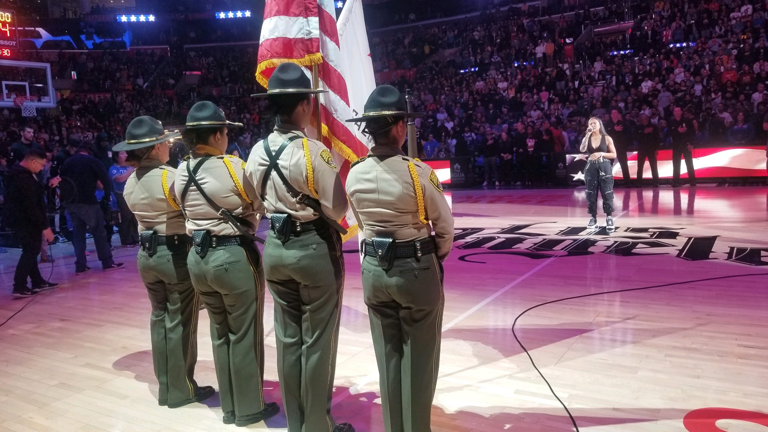 Female officers stand at attention while holding flags.